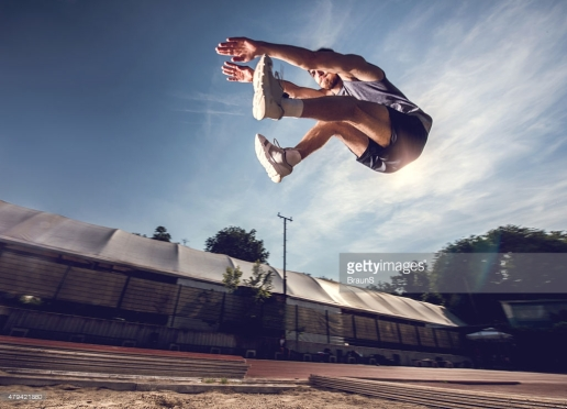 Low angle view of young man in long jump.