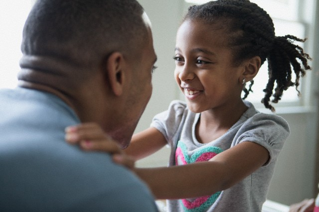 Close-up of young daughter looking into dad's eyes.