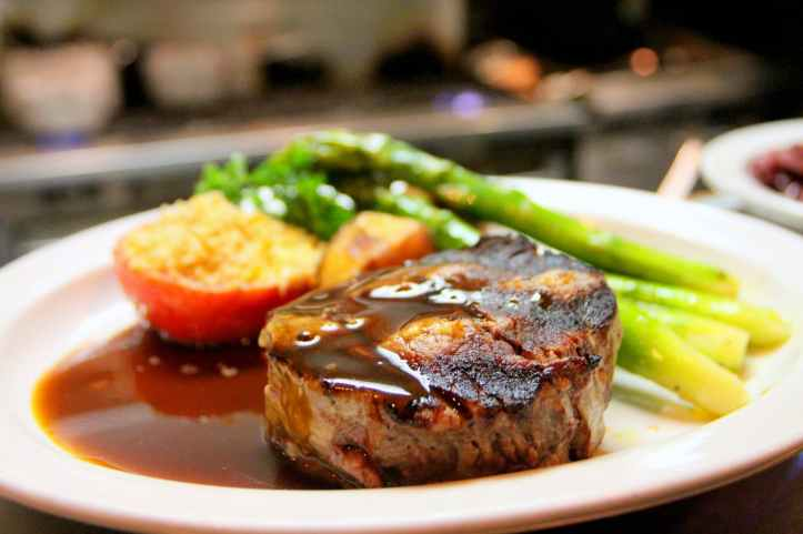 selective focus photography of beef steak with sauce